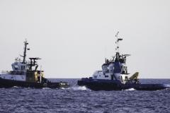 Containerschip wordt getrokken door 2 zeesleepboten